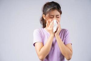 jonge aziatische vrouw veegt haar neus af met een tissue foto