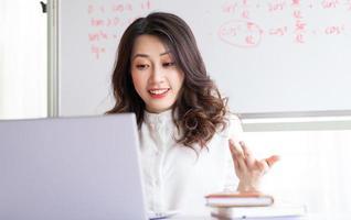Aziatische vrouwelijke leraar die thuis online lesgeeft foto