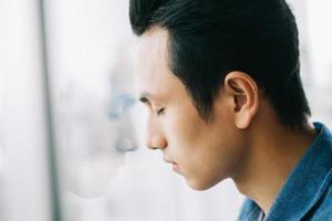 trieste Aziatische man bij het raam foto