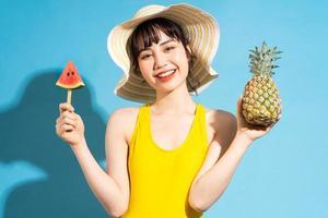 mooie aziatische vrouw die gele jumpsuit op blauwe achtergrond draagt en tropisch fruit eet, zomerconcept foto