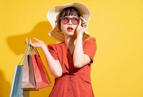 jonge Aziatische zakenvrouw met boodschappentassen poseren op gele achtergrond foto