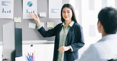 de jonge vrouwelijke directeur werkt een plan uit dat het personeel moet uitvoeren foto