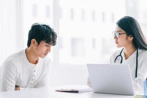 Aziatische vrouwelijke arts controleert de gezondheid van de patiënt foto