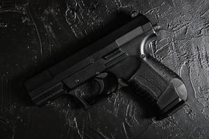 pistool op zwarte textuur tafel. foto