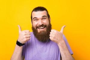 portret van een vrolijke, bebaarde hipster-man die zijn duimen op een gele achtergrond toont foto