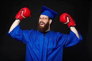 opgewonden bebaarde student man in blauwe vrijgezel vieren met bokshandschoenen foto