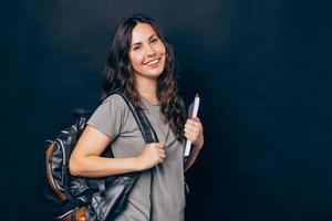 portret van lachende jonge studentenvrouw die over een donkere achtergrond staat en naar de camera kijkt foto