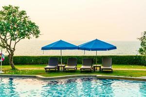 strandstoelen of zwembadbedden met parasols rond het zwembad bij zonsondergang sunset foto