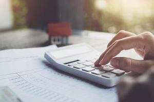 klanten gebruiken pennen en rekenmachines om leningen voor de aankoop van een huis te berekenen op basis van leningdocumenten die ze van de bank hebben ontvangen. onroerend goed concept. foto