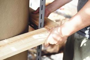 een timmerman meet de planken om de onderdelen te monteren en bouwt een houten tafel voor de klant. foto