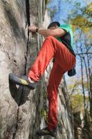 een bebaarde man op leeftijd met een zak magnesia en rotsschoenen wordt getraind op een niet hoge rots in het bos. training van klimmers in natuurlijke omstandigheden foto