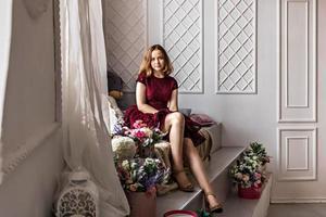 een schattig stijlvol jong meisje in een elegante bordeauxrode jurk zit bij het raam in haar kamer. tiener. afstuderen op school, universiteit foto