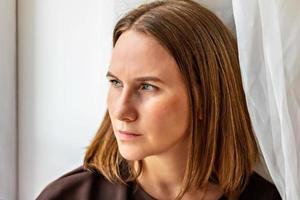 portret van een jonge peinzende vrouw die bij het raam zit. detailopname foto