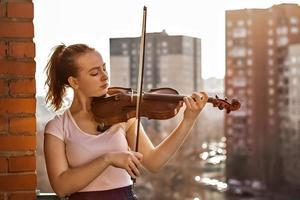 een jong meisje, een muzikant, speelt viool op het balkon van haar appartement foto