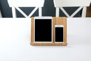 een witte tablet en een smartphone met een zwart scherm op een standaard op een witte tafel. kantoor werkplek foto