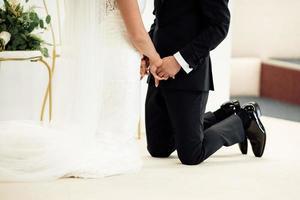 jonggehuwden staande op hun knieën hand in hand en sloten hun ogen. selectieve aandacht. foto