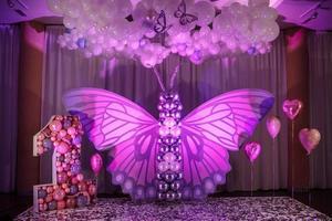 decor van de eerste verjaardag van het meisje. mooie roze fotozone voor een jaar oud babymeisje met grote vlinder van papier en ballen. grote letter nummer één met roze ballonnen. gelukkig verjaardagsfeestje foto