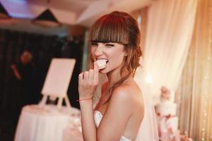 portret van een stijlvolle, vrolijke bruid die een frans macaroondessert eet. bruiloft en vakantie concept foto