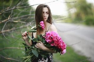 meisje knuffelt een boeket met bloemen. boeket pioenroos. meisje in de bloemen. meisje met een hoed drukt op een groot boeket karmozijnrode pioenrozen. warme zomer zonnige dag buiten de stad buiten foto