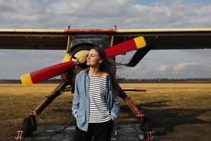 jonge mooie vrouw die zich dichtbij het vliegtuig bevindt. reizen en technologie. foto
