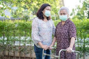 aziatische senior of oudere oude dame vrouw loopt met rollator en draagt een gezichtsmasker ter bescherming van de veiligheidsinfectie covid-19 coronavirus. foto
