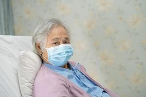aziatische senior of oudere oude dame vrouw patiënt draagt een gezichtsmasker nieuw normaal in het ziekenhuis ter bescherming van de veiligheidsinfectie covid-19 coronavirus. foto