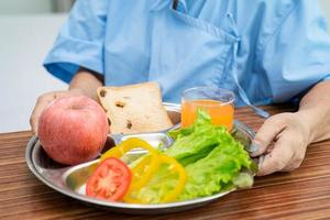 Aziatische senior of oudere oude dame vrouw patiënt ontbijt plantaardig gezond voedsel eten met hoop en gelukkig zittend en hongerig op bed in het ziekenhuis. foto