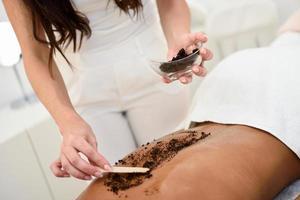 vrouw reinigt de huid van het lichaam met koffiescrub in het spa-wellnesscentrum. foto