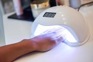 gemanicuurde nagels in uv-lamp in schoonheidssalon. foto