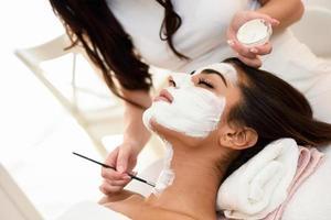 esthetiek een masker aanbrengen op het gezicht van een mooie vrouw foto