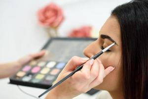 visagist die make-up op de wenkbrauwen van een vrouw aanbrengt foto