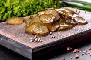 smakelijke zoute pittige ingelegde komkommer gesneden met ringen op een houten snijplank foto