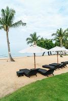 lege strandstoel met palmbomen op het strand met zee achtergrond foto