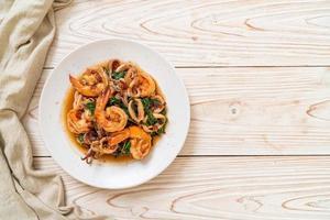 roergebakken zeevruchten van garnalen en inktvis met thaise basilicum - Aziatisch eten foto