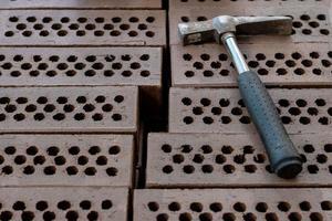 een hamer wordt op een rode bakstenen stapel gelegd. foto