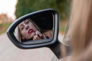 een jonge, mooie vrouw met lang haar kijkt in de achteruitkijkspiegel van de auto en schildert haar lippen. foto