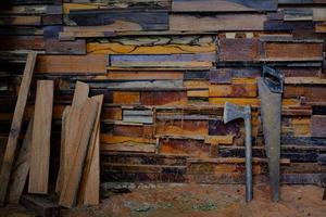 bijl met metalen handvat en handzaag die tegen oude muren rust, zijn gemaakt van verschillende houtsoorten foto