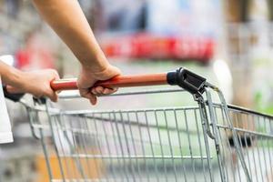 close-up van man duwen winkelwagentje in een supermarkt a foto