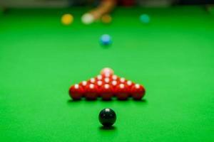 speler schoot bal op groene snookertafel foto