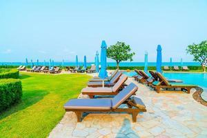 stoelzwembaden of bedden en parasols rond het zwembad met zeeachtergrond - vakantie en vakantieconcept foto