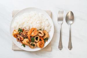 rijst en roergebakken zeevruchten van garnalen en inktvis met thaise basilicum - Aziatisch eten foto