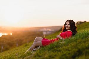 mooi jong meisje zittend op een helling bedekt met groen gras foto
