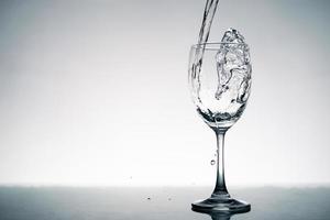 close-up van plons kristalhelder water dat in het wijnglas op tafel stroomt. foto