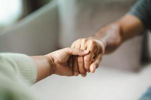 vrouwelijke vriend of familie hand in hand tijdens het opvrolijken van de mentale depressieve man, psycholoog biedt mentale hulp aan de patiënt. ptss geestelijke gezondheidsconcept foto