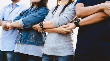 close-up van vriendenteam dat elkaars gekruiste handen, vriendschap en teamwerkconcept vasthoudt. foto
