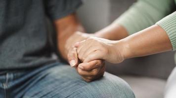 vrouwelijke vriend of familie zitten en houden elkaars hand vast tijdens het opvrolijken van de mentaal depressieve man, psycholoog biedt mentale hulp aan de patiënt. ptss geestelijke gezondheidsconcept foto
