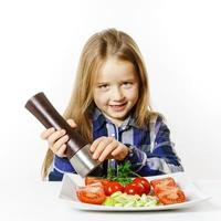 schattig klein meisje met salade en peperdoos foto
