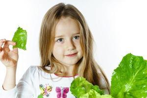 schattig klein meisje poseren met verse slablaadjes foto