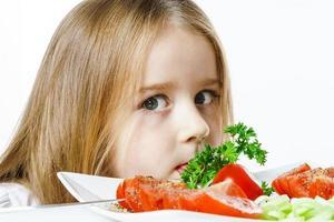 schattig klein meisje met bord verse groenten foto