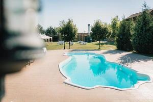 blauw buitenzwembad in de tuin omgeven door bomen foto
